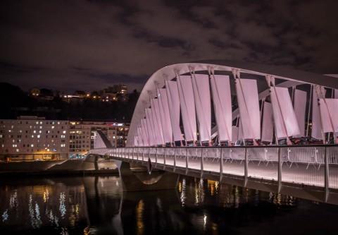Sous le vent, le Pont Schuman illuminé De grandes voiles blanches arrimées aux suspentes de la structure du Pont vont battre sous le vent. Cette installation met en valeur le volume formé par les quatre grandes arches du pont Schumann.D'immenses kakémonos blancs sont fixés aux haubans. Ils sont les points […]